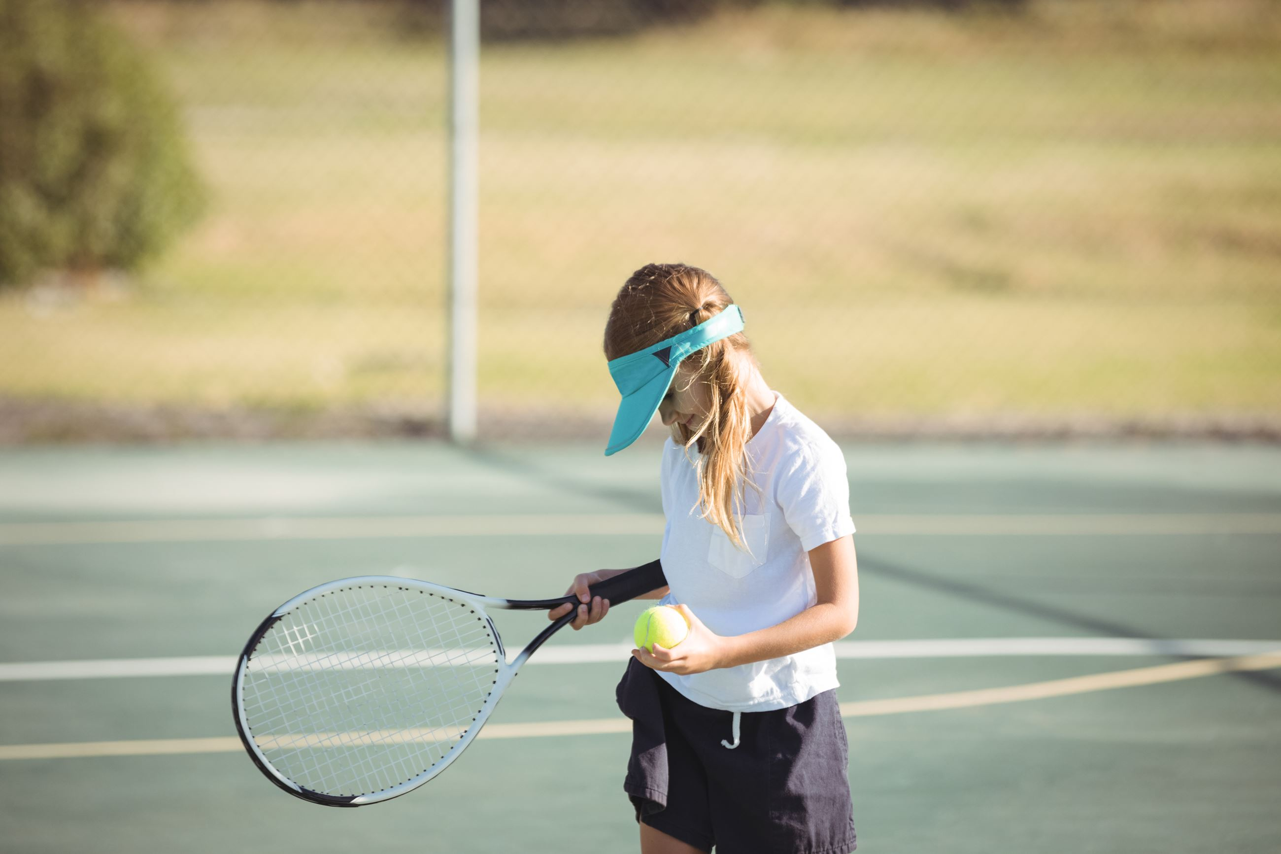 girl holding tennis ball and racket on court